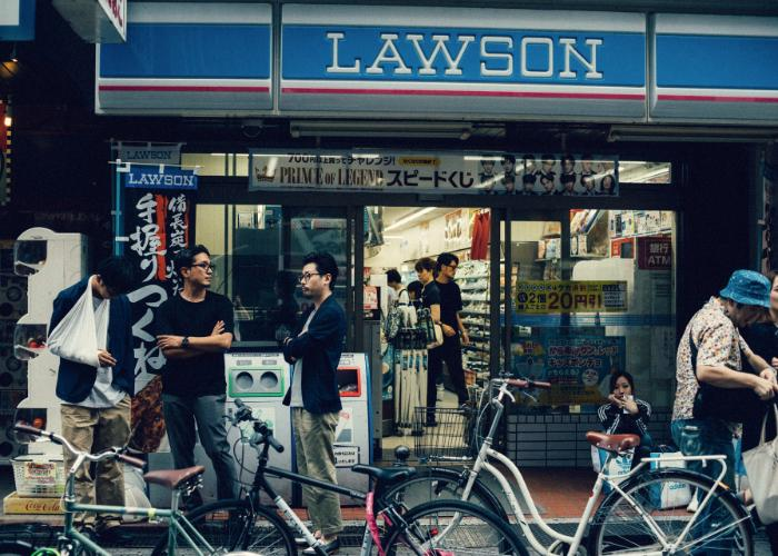 Lawson convenience store exterior with a group of three men outside