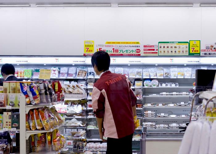 7-Eleven interior, a worker walks through the stocked shelves