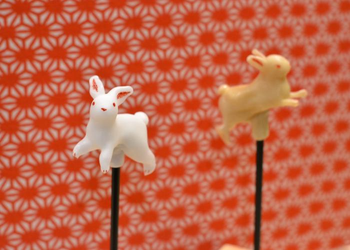 Two Japanese amezaiku candy rabbits against a red backdrop