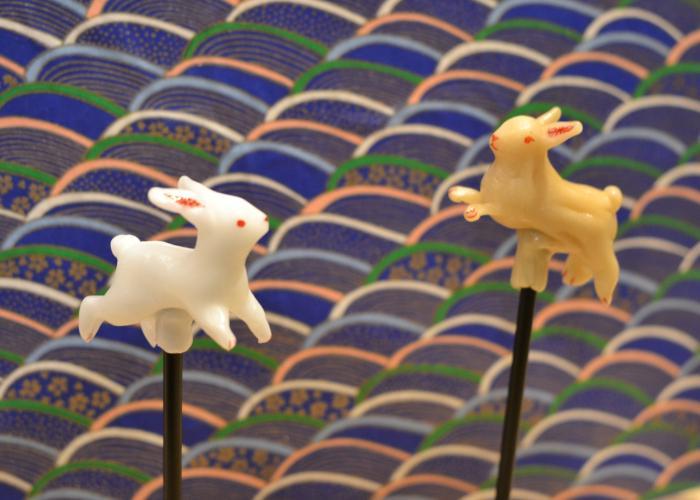 Two Amezaiku rabbits (Japanese Candy Sculpture) against a traditional Japanese-patterned backdrop