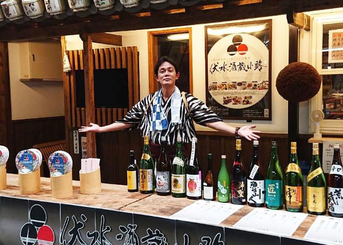 The barman of Fushimi Sakagura Koji stands behind the counter with his arms open, and 15 bottles in a row in front of him.