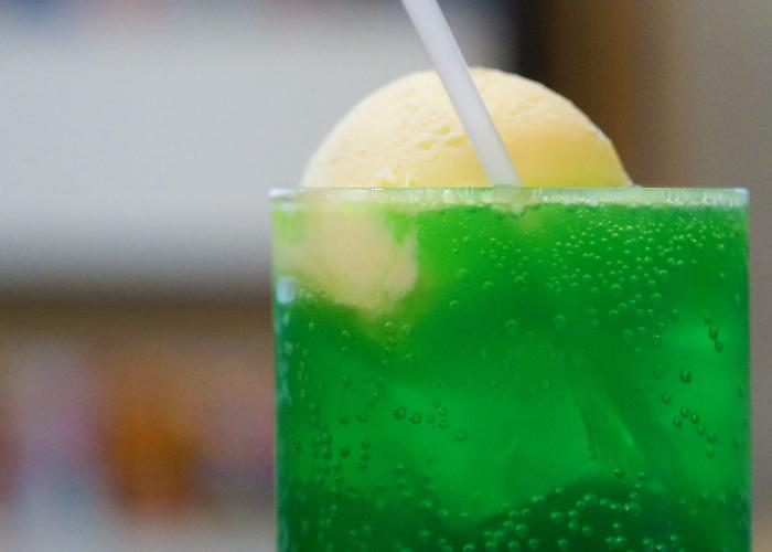 A popular Japanese beverage, a glass filled with vibrant green melon soda
