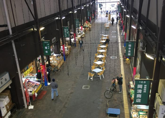 Yellow tables and chairs under cover of the Osaka Kizu Wholesale Market arcade