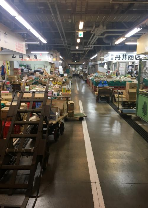 Interior of the Osaka Kizu Market with stacks of boxes containing vegetables and fish