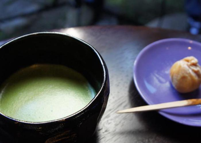 Japanese green tea in black cup, Japanese round food on blue plate with toothpick