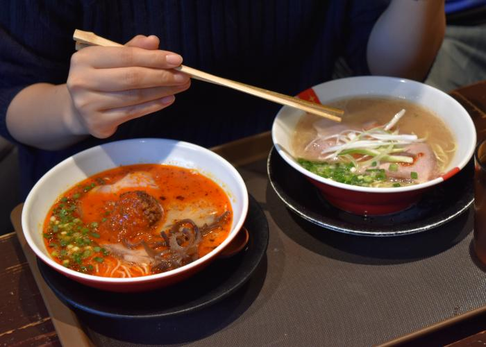 Two mini bowls of ramen, one with a bright red broth, the other with a light-colored broth, during a ramen food tour in Tokyo