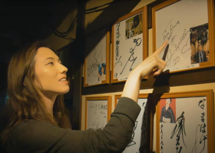 Shizuka points out David Beckham's signature and photo at the Akita Namahage Restaurant in Ginza