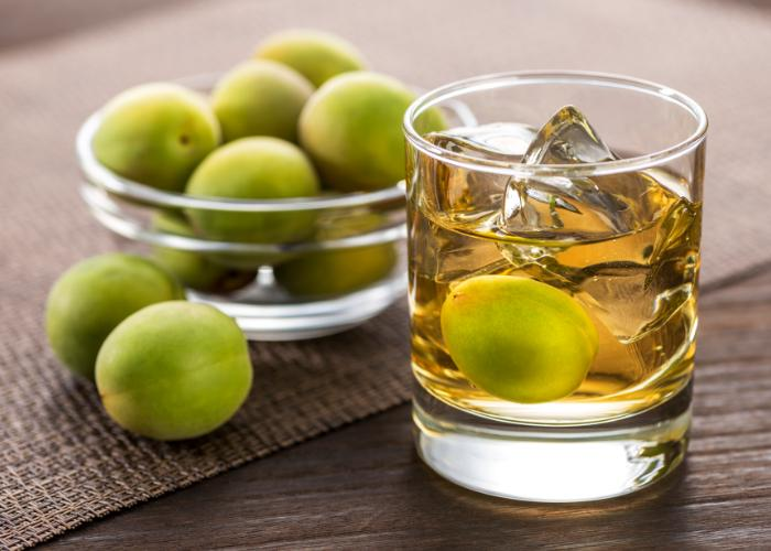 Japanese umeshu plum wine. A bowl of green Japanese ume plums and a cup of amber liquid