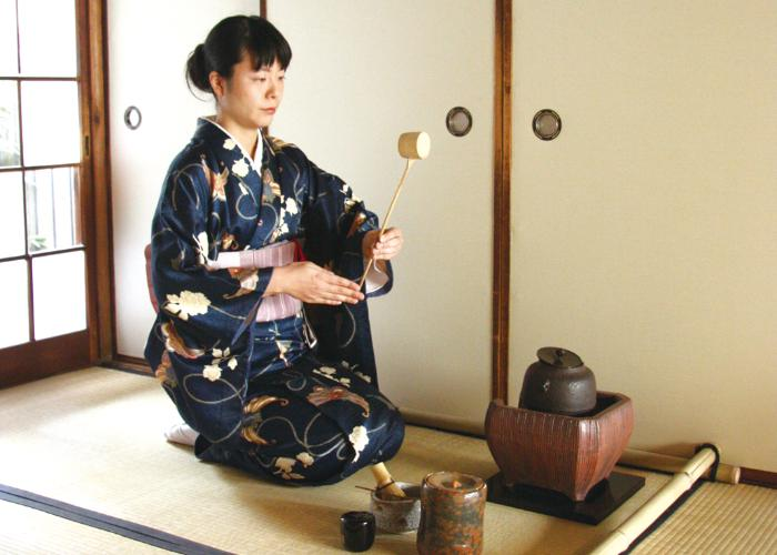 Woman holding a bamboo ladle for Kyoto tea ceremony