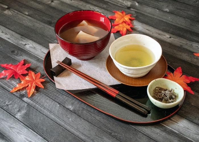 Green tea, miso, and side dish in small Japanese dishes on serving tray among red-orange fall leaves