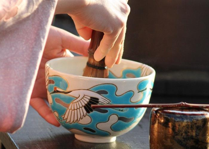 Hand with kimono sleeve stirring tea with bamboo tea whisk in blue-white cup with heron on it