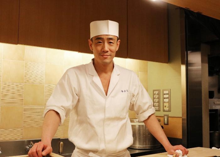 A young Japanese sushi chef in his white uniform leans on the wooden counter