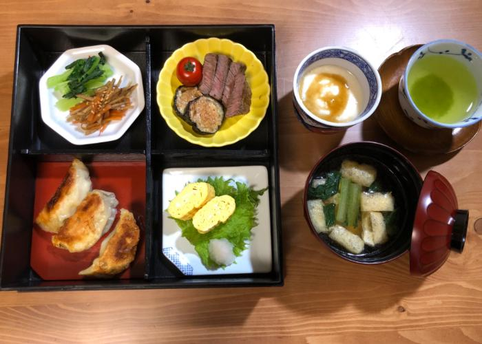 Several plates from above, featuring gyoza dumplings, wagyu beef,  rolled egg omelet, and various vegetable dishes.