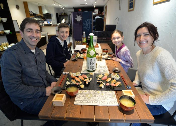 Family of four sits down to a meal of homemade nigiri sushi and smiles