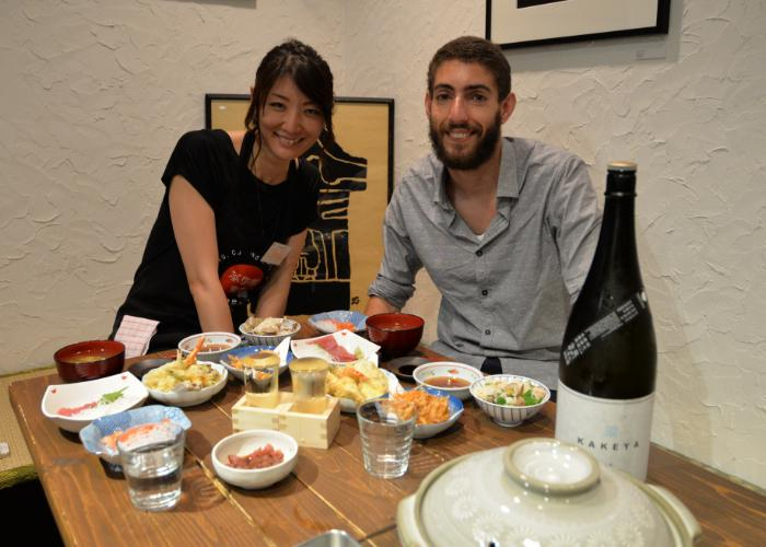 A man and a woman sitting at a table with a spread of Japanese food smile at the camera