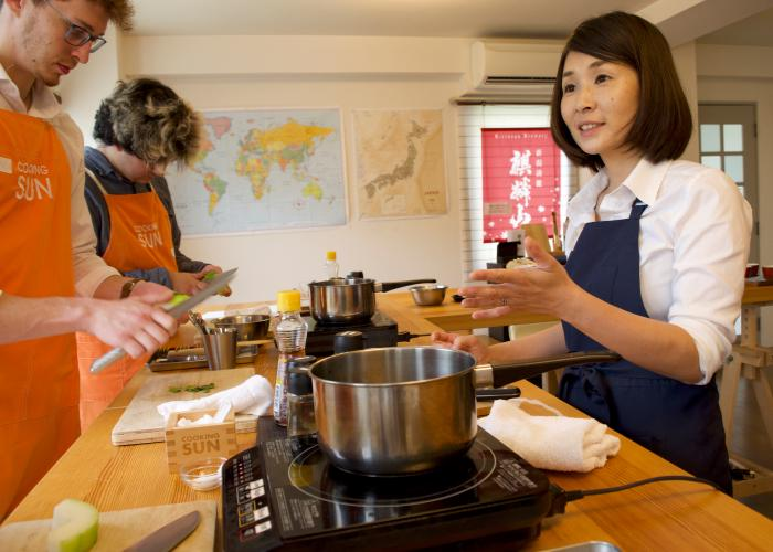 Japanese cooking teacher chats to her students as they cut vegetables