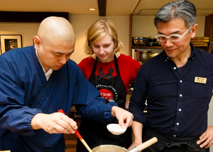 A Japanese cooking instructor shows a couple what to do with their pot of food.