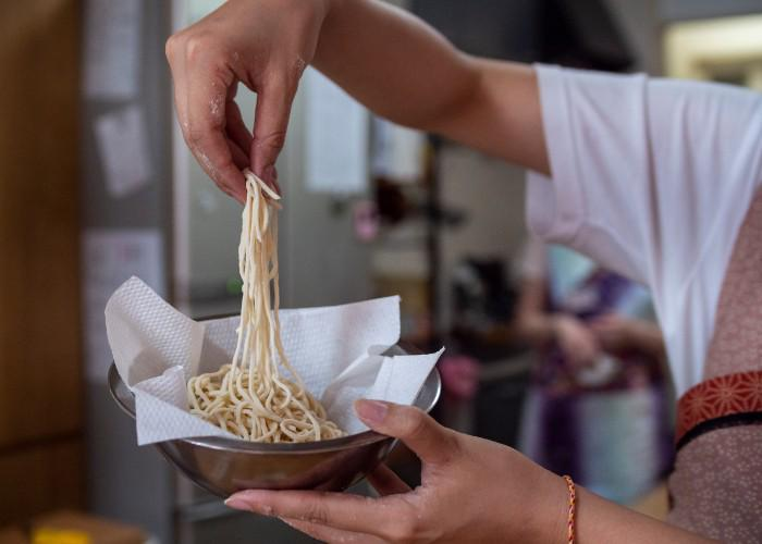 A man holds up a bunch of ramen noodles above a straining bowl with kitchen paper lining.