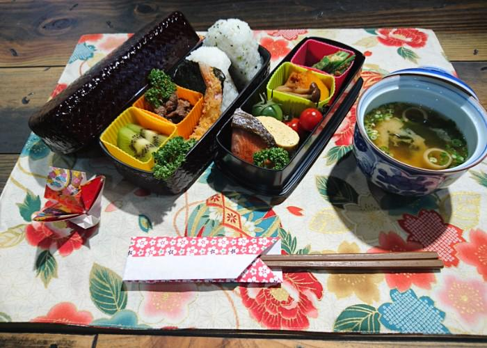 A nicely patterned bento box sits on a table wit its lid off, showing a range of colorful foods stuffed inside.