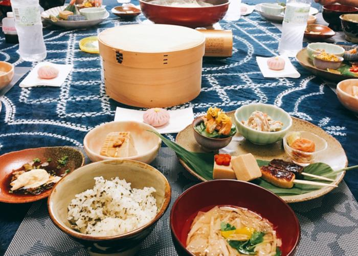 Bowl or rice, sesame tofu, soup, and various other umami Japanese dishes spread on a table