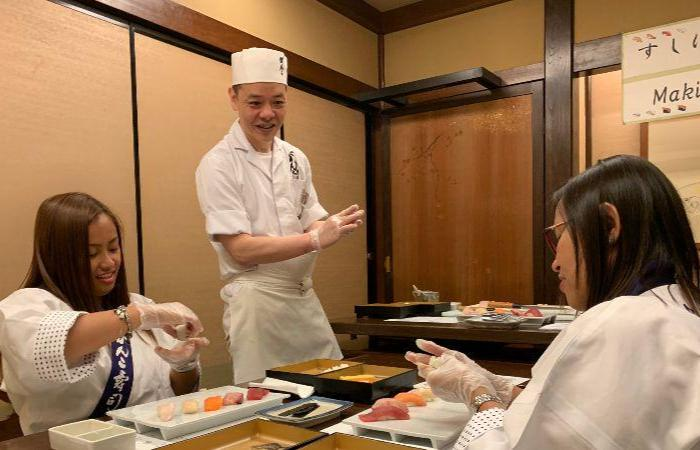 A smiling sushi cooking instructor watches over two students who are molding their nigiri sushi into shape.