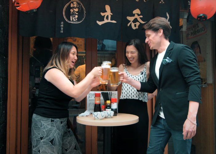 A man and two woman clink beer glasses outside a standing bar in Shibuya, with red hanging lanterns outside