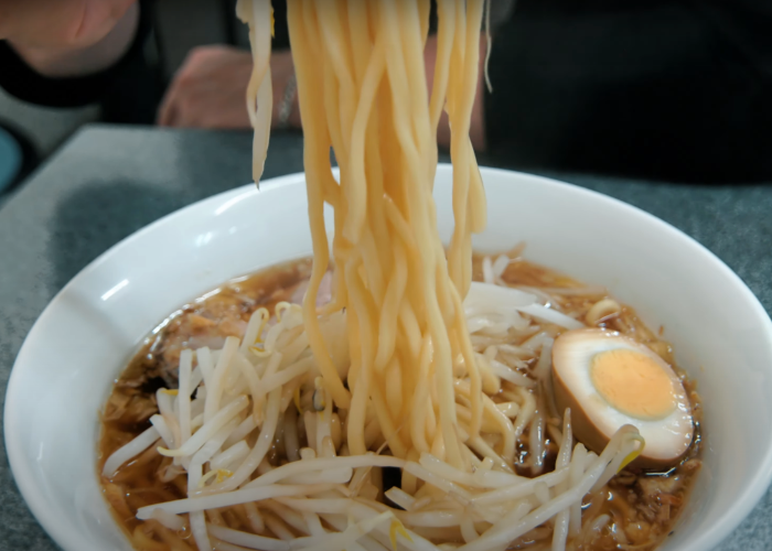 Ramen noodle pull out of a bowl of intense and flavorful shoyu ramen