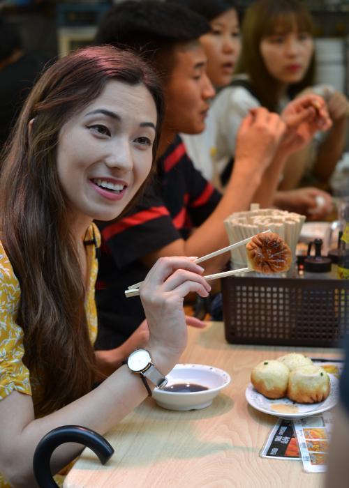 Shizuka Anderson in Ameya Yokocho Market eating a yaki shoronpo (pan-fried soup dumpling), a classic street food