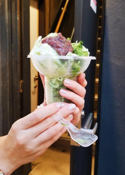 Japanese Kakigori at Ameyoko Market in Ueno, a heaped pile of shaved ice topped with matcha syrup and red bean