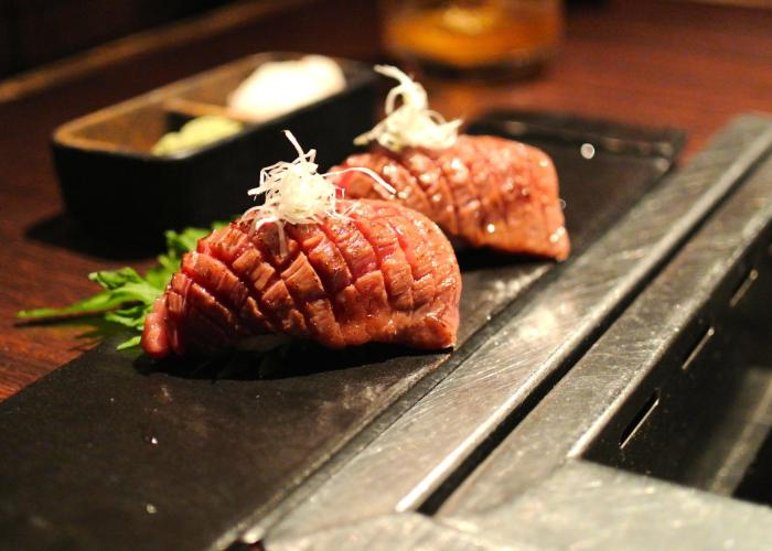 2 morsels of cooked Matsusaka beef on a plate at a restaurant