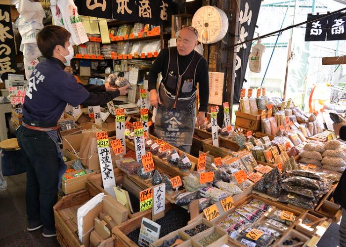Two sellers at Tsukiji Market talk at their dried food stand