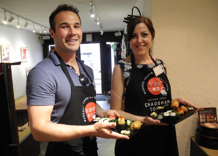 A man and a woman hold out trays of vegetable nigiri sushi made during a Vegetarian Sushi Making Class in Tokyo