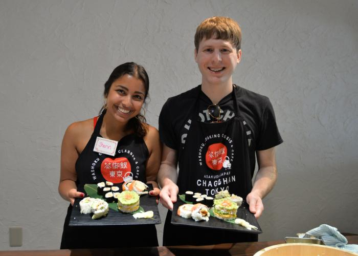 A man and a woman hold out trays of their sushi rolls and mille-feuille sushi