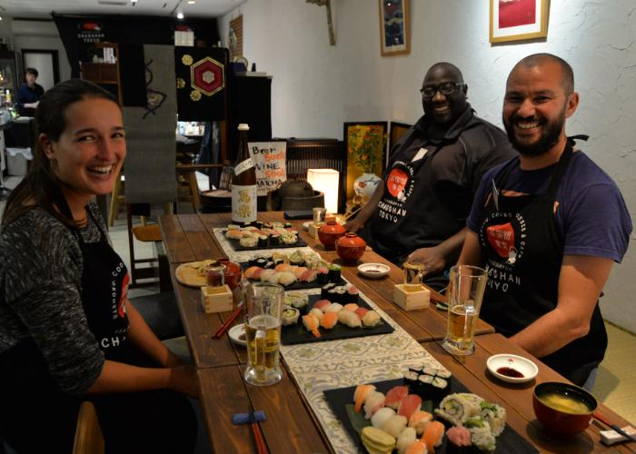 A woman and two men with plates of nigiri sushi in front of them smile during a Nigiri and Rolled Sushi Making Class in Tokyo
