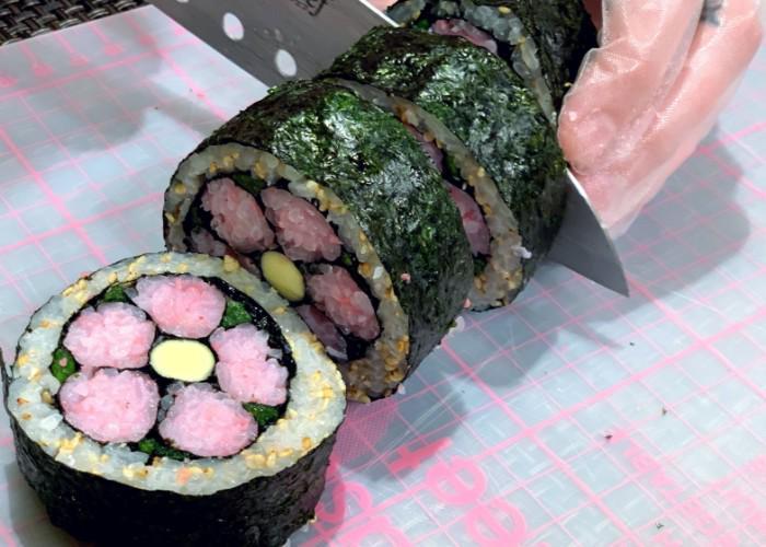 Knife cuts through sushi roll during Decorative Sushi Making Class