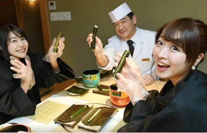 Two girls smiling and holding up sushi during Tokyo Sushi Making Class with a Professional Chef