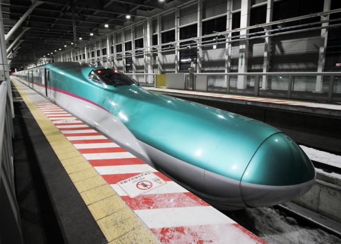JR East Shinkansen Hayabusa green bullet train stopped at a station