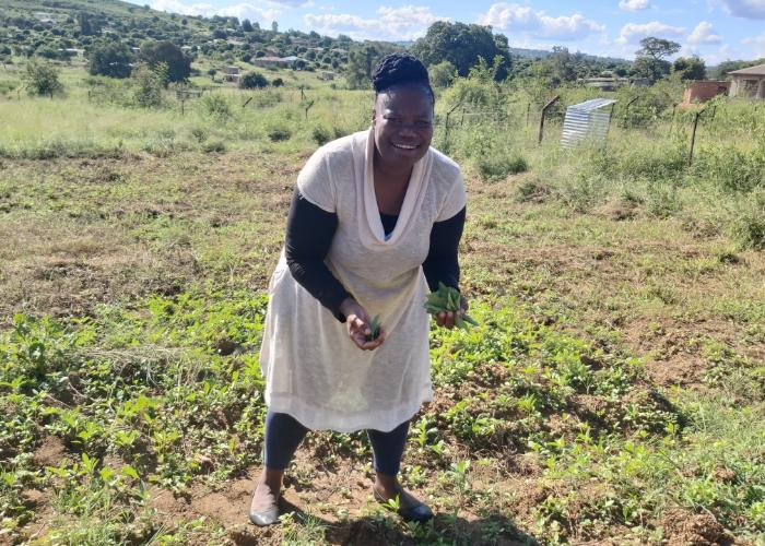 A South African woman stands in a field, smiling and holding vegetables she harvested