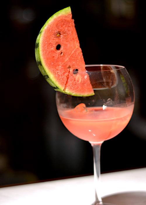 Watermelon shochu cocktail in a long-stemmed glass with a slice of watermelon rimming the glass