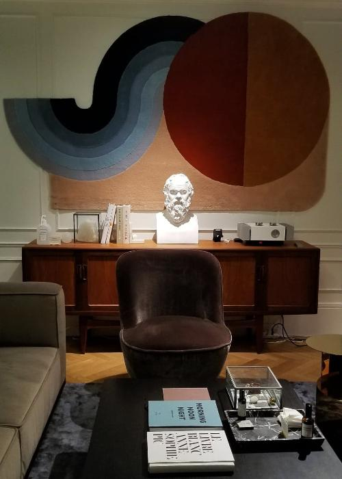 A couch sits to the left with a coffee table and books in front of it. To the back is a colorful wall hanging and the bust of a man