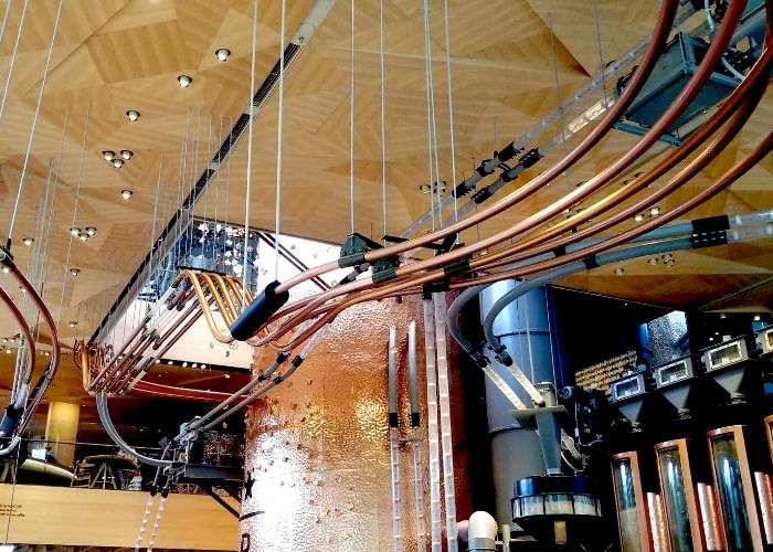 Interior of the Starbucks Reserve Roastery Tokyo, a ceiling with twisting pipes