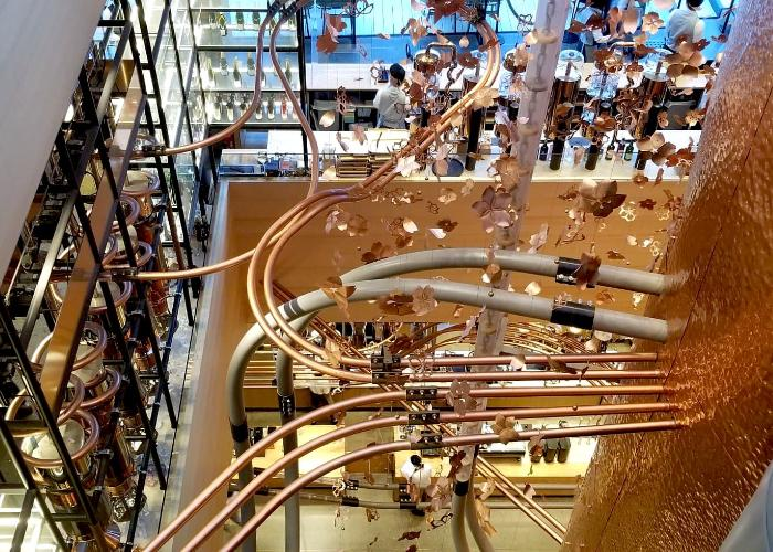 Starbucks Reserve Roastery Tokyo showing the layout of the store with several floors, twisting pipes, and metal sakura petal decor
