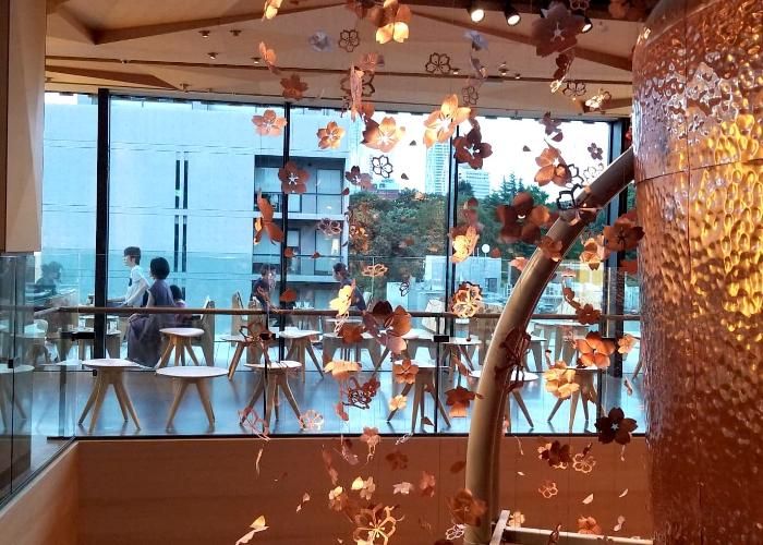 Interior of Starbucks Reserve Roastery Tokyo with metal sakura petals cascading from the ceiling