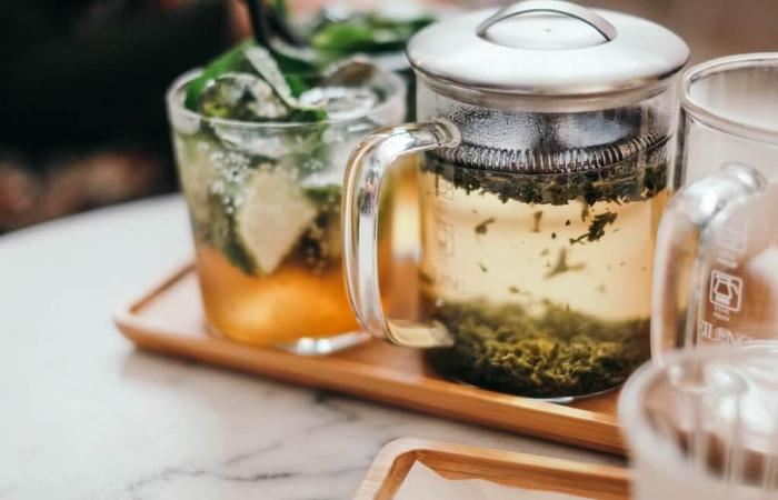 A beaker infused with tea leaves and a tasty looking cocktail in a glass