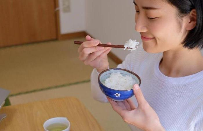 Woman wearing a white shirt eating white rice