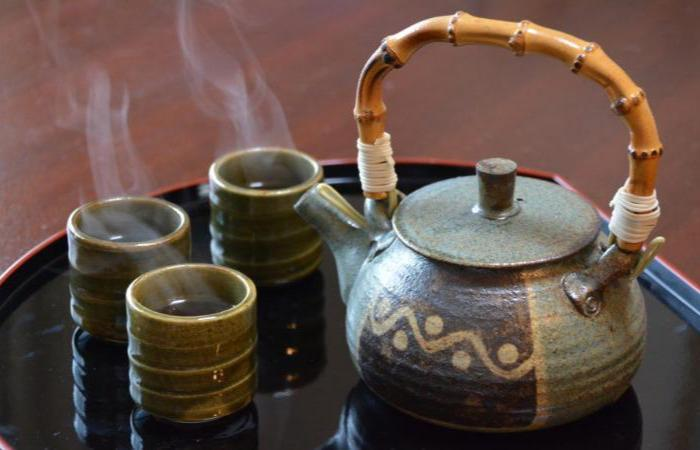 A Japanese-style tea kettle and three steaming cups