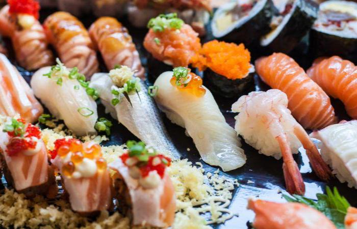 A platter of colorful nigiri sushi arranged in neat rows