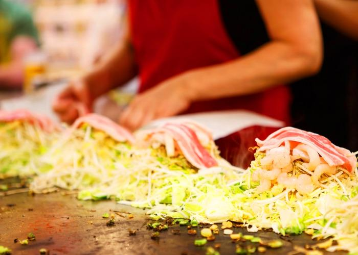Hiroshima style okonomiyaki being grilled on the teppan