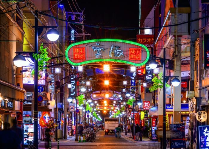 Backstreets of Hiroshima city at night, with neon signs aglow
