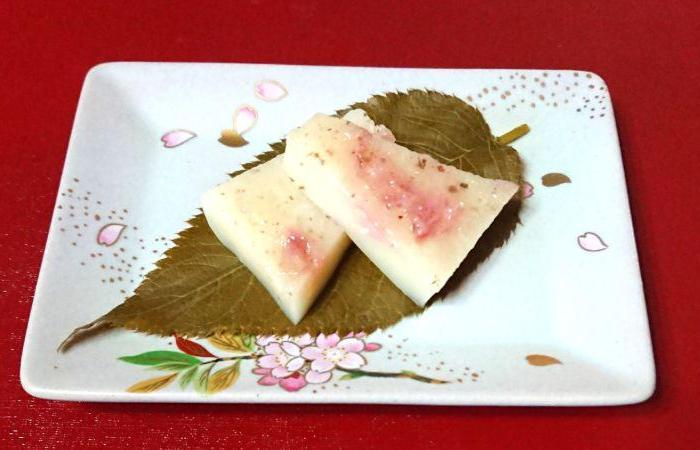 Two rectangular pink sakura Japanese sweets plated on square white floral plate atop leaf